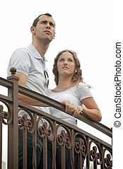 young couple looking up to the sky from outside balcony -...