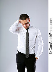 Portrait of a pensive businessman in glasses on gray...