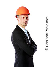 Handsome businessman in helmet standing with arms folded...