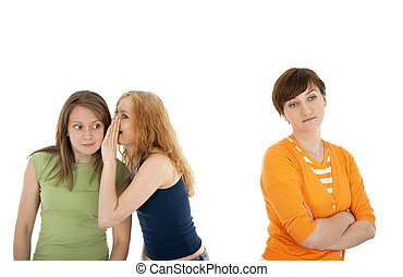 Rejected friend - Two girls whispering secrets to each...