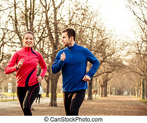 Couple jogging together - Young couple jogging together in...