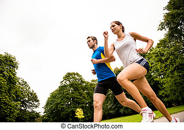 Jogging together - young couple running - Fitness couple -...