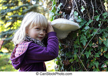 little girl and Tinder fungus - Little caucasian girl...