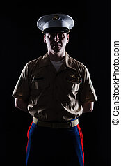 Contour shot of US marine in blue dress uniform on black...