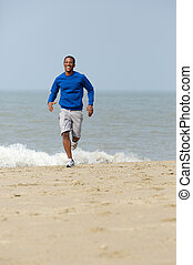 Man smiling and jogging at the beach - Athletic young man...