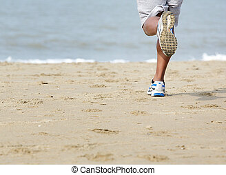 Rear view of man jogging at the beach - Low angle rear view...