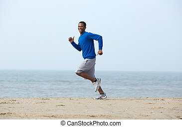 Smiling man jogging at the beach - Smiling young man jogging...