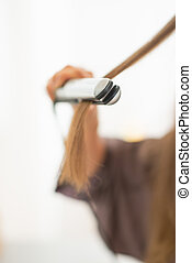 Closeup on young woman using hair straightener