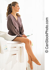 Relaxed young woman with toothbrush in bathroom