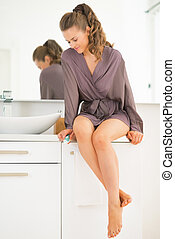 Young woman with toothbrush in bathroom