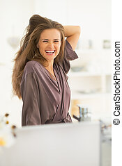 Portrait of happy young woman with long hair looking -...
