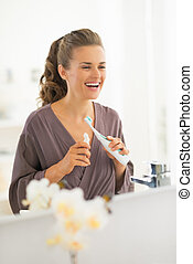 Happy young woman with toothbrush in bathroom