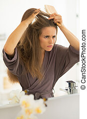 Concerned young woman combing hair in bathroom