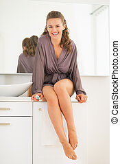 Smiling young woman with toothbrush in bathroom