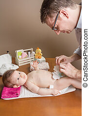 Father changing diaper of adorable baby with a hygiene set...