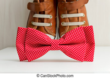 Bow tie and sneakers Brown sneakers and red bow tie with...