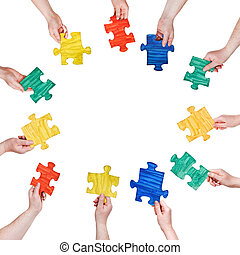 painted puzzle pieces in people hands in circle - set of...