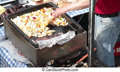 Frying vegetables for hamburgers - Middle aged caucasian man...