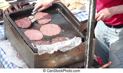 Frying meat for hamburgers - Middle aged caucasian man...
