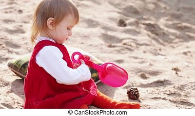 Little girl on sand with toys