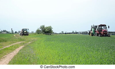 farm tractor fertilizing - farm tractor rides through crops...