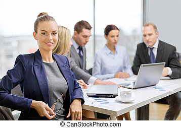 businesswoman with glasses with team on the back - business,...