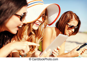 girls with tablet pc on the beach - summer holidays,...
