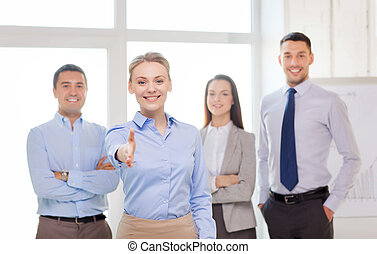 smiling businesswoman in office with team on back - business...