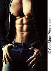 abdominals - Sexual muscular young man over dark background....
