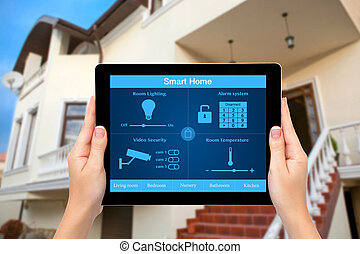 Female hands hold a tablet computer with system smart house...