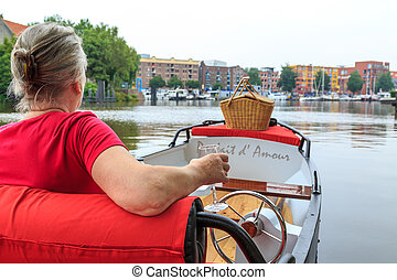 Woman in boat with picnic basket - Woman sitting in boat...