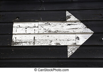 white arrow painted onto a black wooden shed wall - peeling...