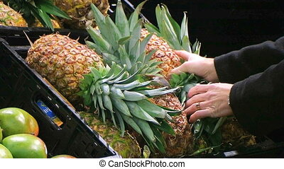 Woman Selects Pineapple - Woman selecting pineapple in...