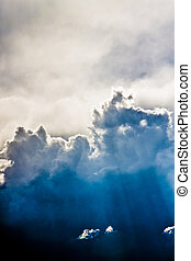 Rays of Sun From Above Towering Clouds Background