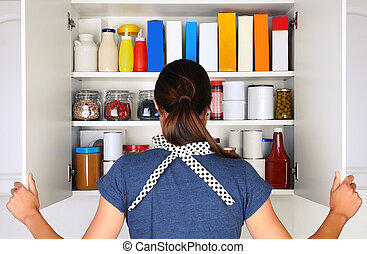 Woman Opening Full Pantry - A woman seen from behind opening...
