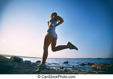 Girl running - Photo of young woman running on the beach at...