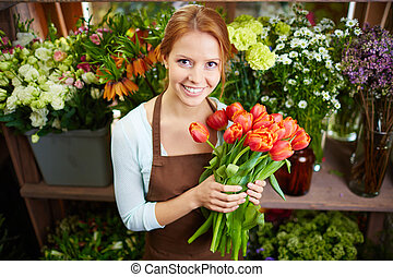 Pretty florist - Portrait of young female florist with red...