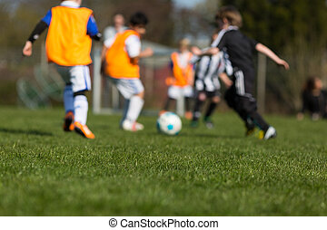 Children playing soccer - Two teams of children playing a...