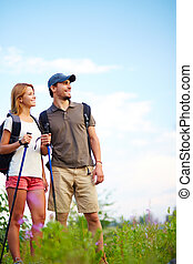 Adventure lovers - Couple of smiling trippers standing in...