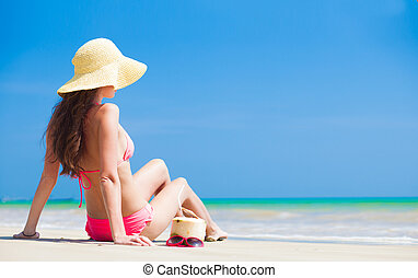 Happy young woman in straw hat and bikini with coconut on the beach