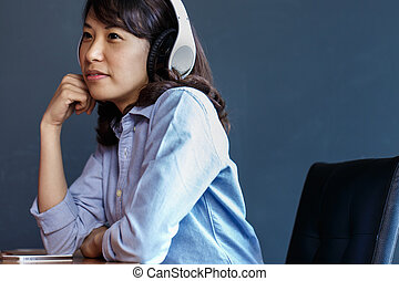 Young woman using wireless headphone at work