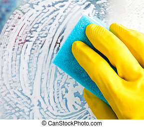 House chores - Hand in yellow protective glove cleaning...