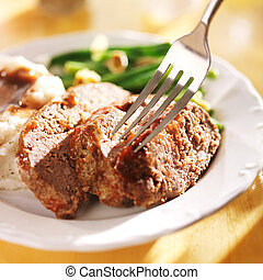 eating a meatloaf dinner with a fork