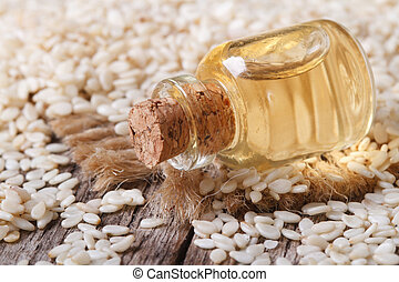 sesame seed oil in glass bottle on the table horizontal -...