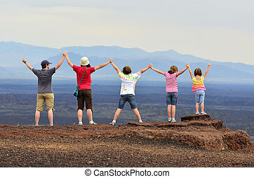 Family Enjoying View on Vacation - Family holding hands and...