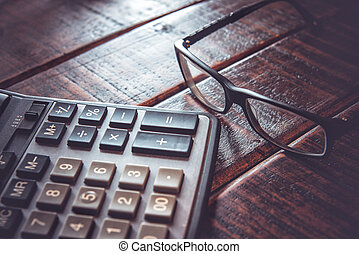 Calculator and glasses on wooden table