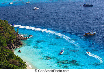 Aerial view of a beach with some motorboats in the turquoise...