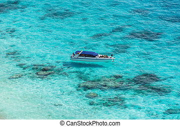 Aerial view of the tropical island, clear blue sea and a boat on a sunny day