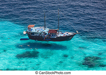 Aerial view of the tropical island, clear blue sea and a tourist boat on a sunny day