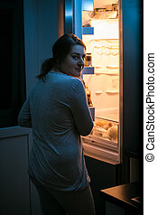 photo of woman looking in fridge at late night